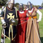 Three people in medieval dress wearing helmets